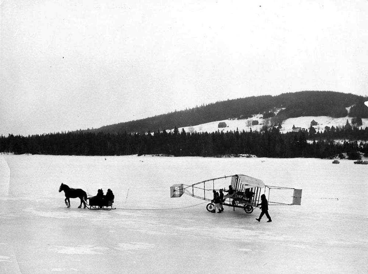 Ett fly på hjul på isen som blir trukket av en hest med vogn. Silver Dart II. Flere personer i vognen og rundt flyet. Fjell i bakgrunnen.