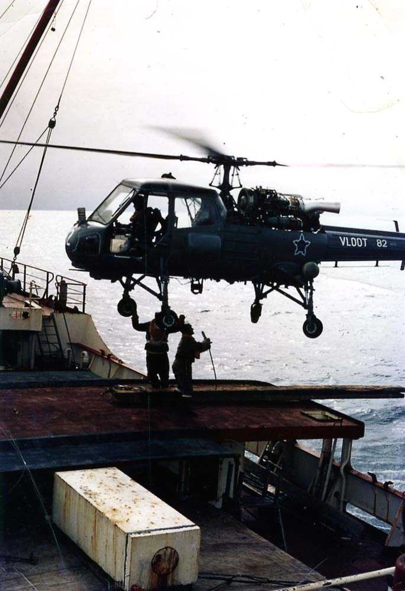 Ett helikopter i luften over dekket til en båt. Westland  Wasp fra Sør-Afrika. To personer på dekk under helikoptret.