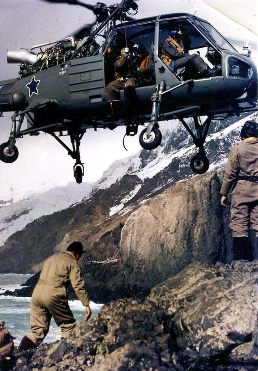 Ett helikopter i luften like over bakken, Westland Wasp fra Sør-Afrika. To personer under helikoptret på bakken.