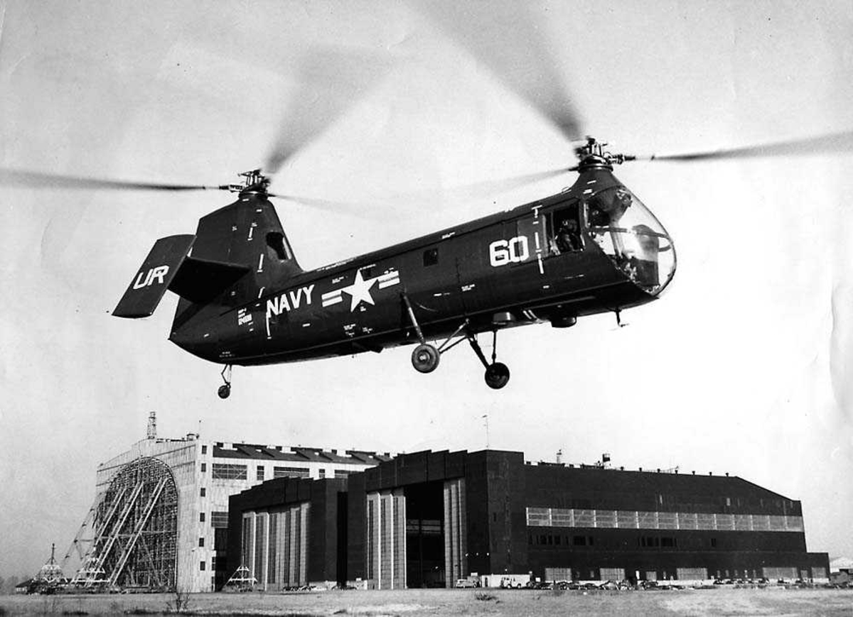 Luftfoto. Ett helikopter i luften like over bakken, Piasecki PV-14 HUP-1. Bygninger i bakgrunnen.