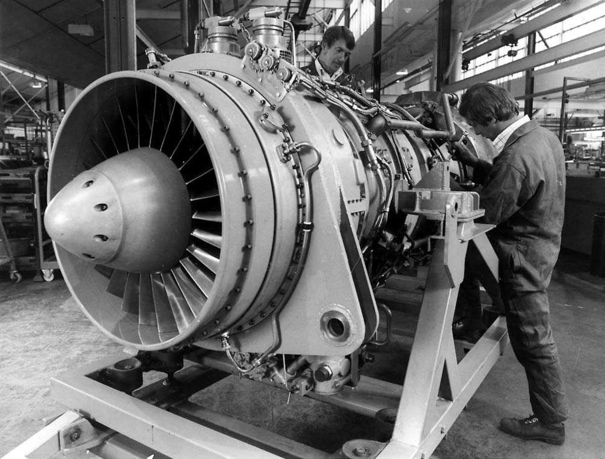 En motor inne i et verksted, Rolls-Royce Marine Spey. To personer jobber med motoren.