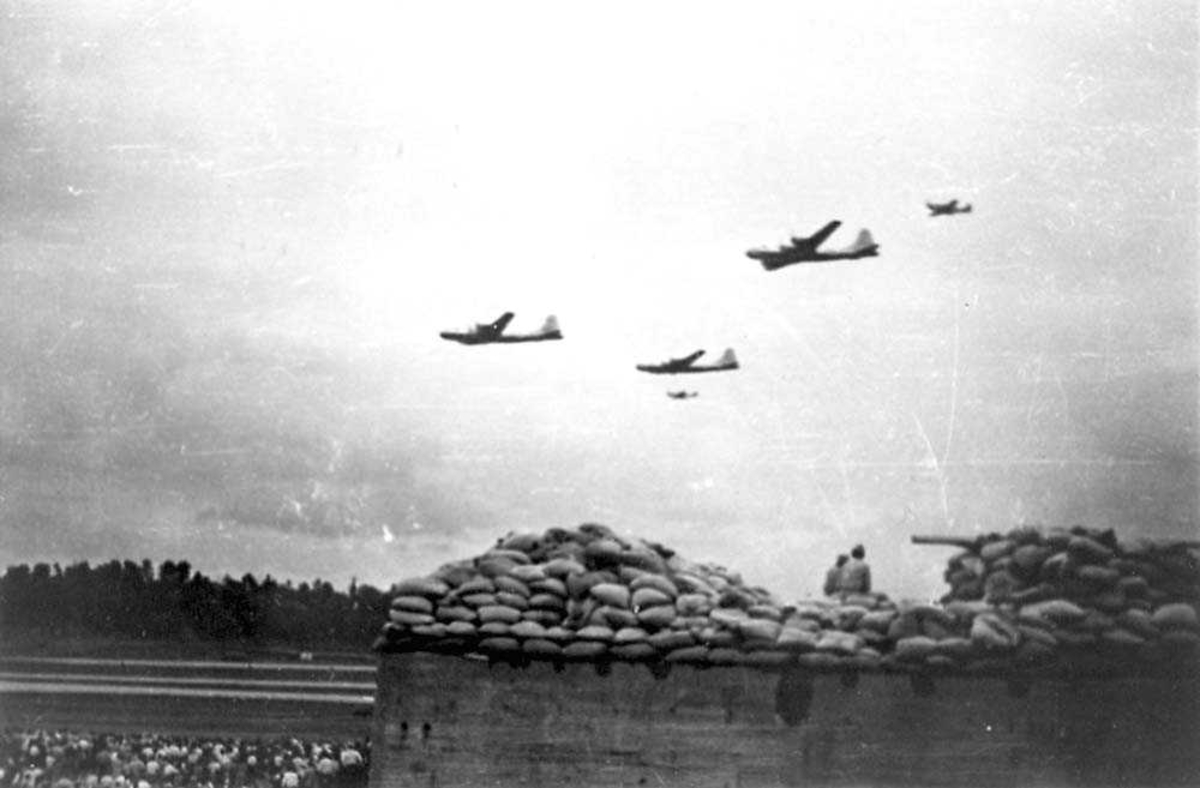 Luftfoto. Fem fly i luften. Folkemengde som står å ser på. Festning/kanonstilling i forgrunnen. Tre B-29 og to F-51 Mustang i luften