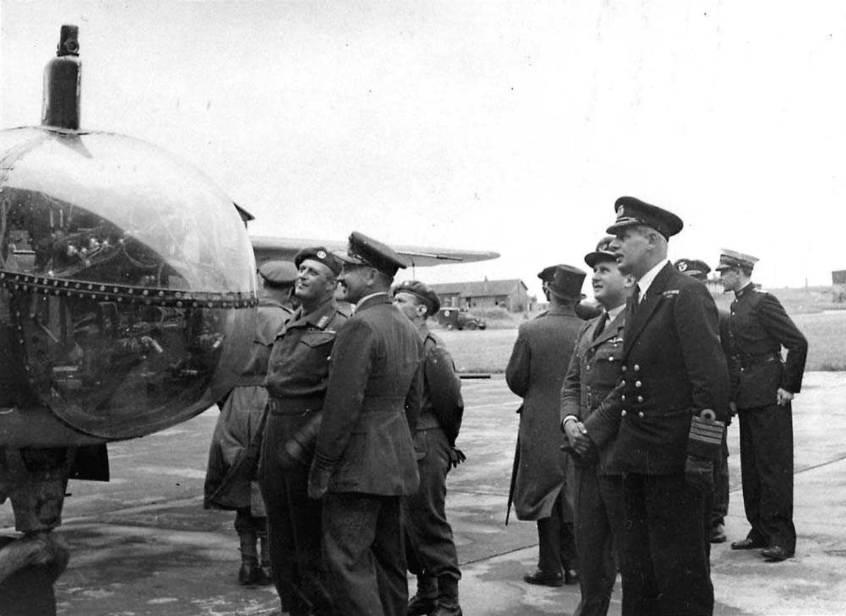 Flere personer som ser på et fly, bl.a. Kronrpins Olav.