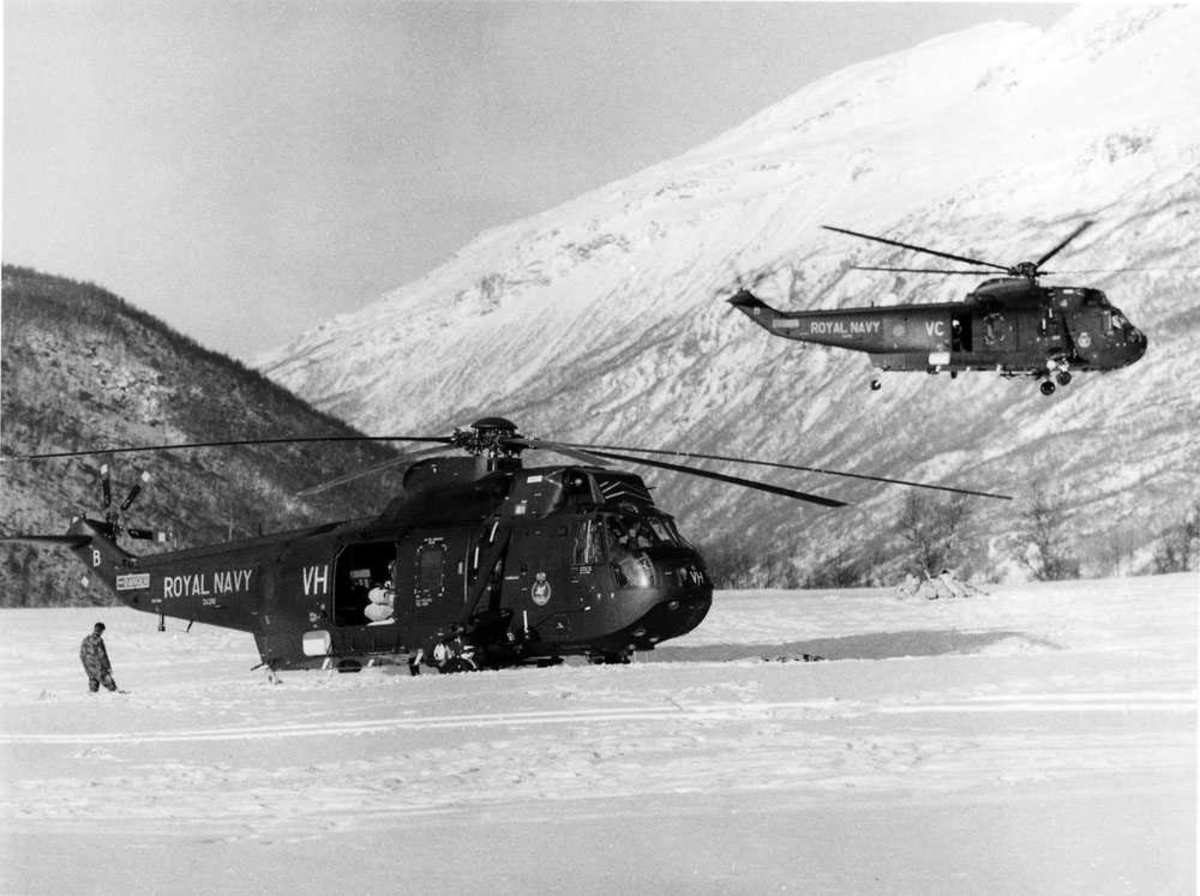 Ett helikopter på bakken t.h., ett helikopter i luften. En person t.h. for helikopteret på bakken. Westland Sea King HC Mk.4, tilhørende Royal Navy. Helikopteret på bakken er merket ZA292/VH. Helikopteret i luften er merket VC (muligens ZD477/VC)