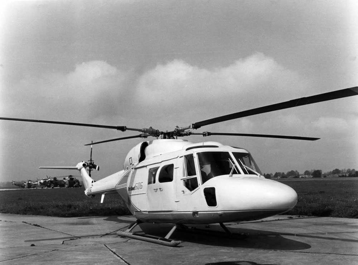 Ett helikopter på bakken. Westland 606 (Lynx). Fire Westland Sea King skimtes t.h bak i bildet, tre tyske og en engelsk.