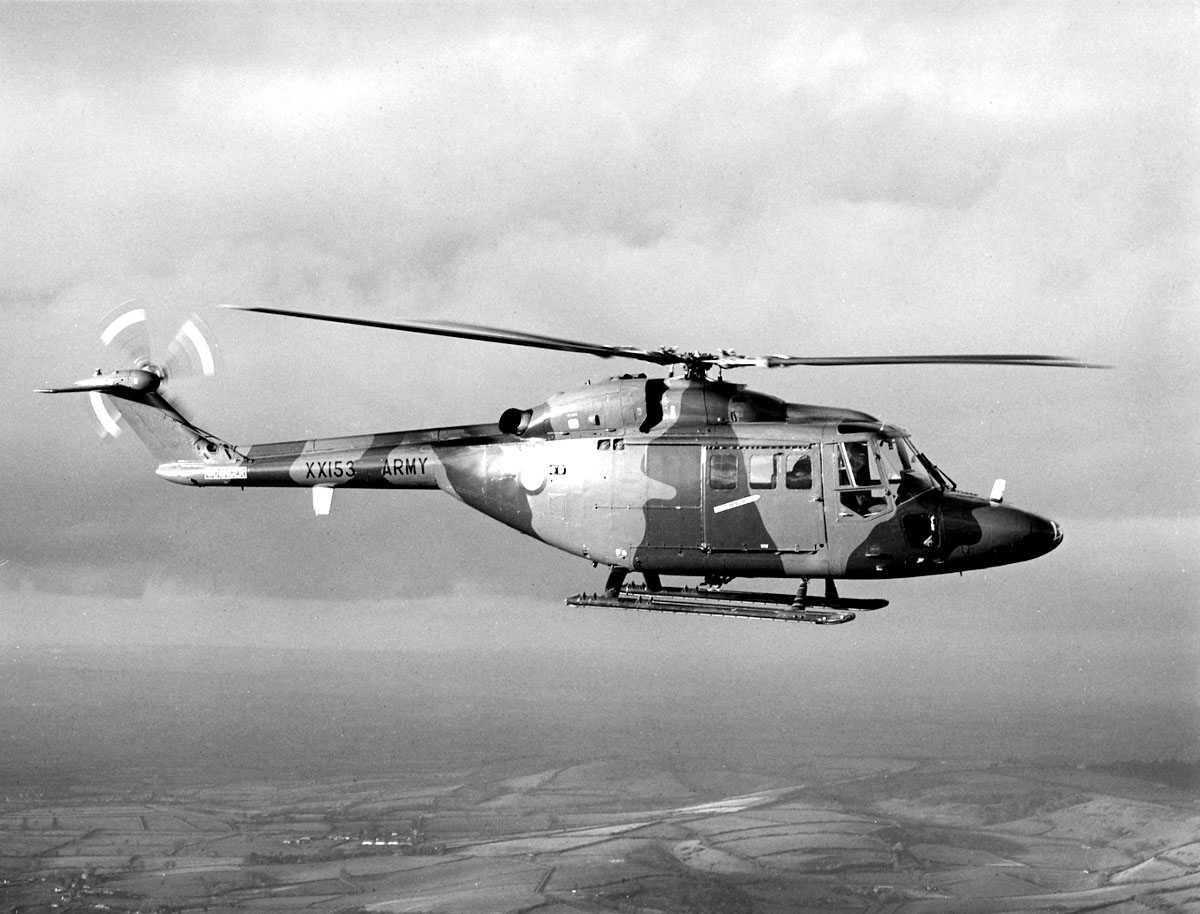 Ett helikopter i luften, over landbruksområder. Westland Lynx AH Mk.1. Halebjelke merket XX153 ARMY. Kamuflasjefarger.