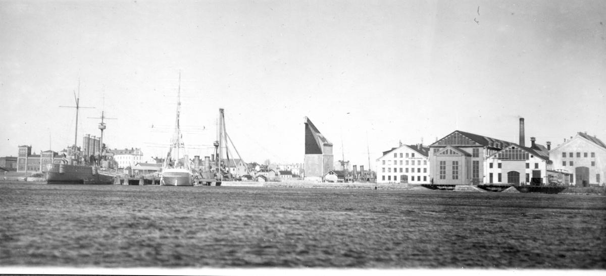 Ingenjörsdepartementets verkstäder med Pansarskeppet Fylgia och övningsfartyget Chapman vid utrustningspiren. Pansarskeppet Oscar II och torpedkryssaren Jacob Bagge på vänster sidan.