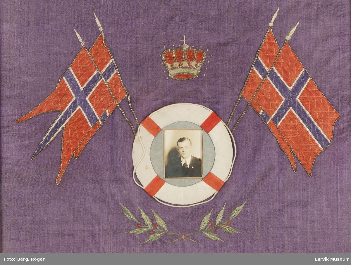Norske flagg aplikert på fiolett silkestoff. Hvit livbøye med krone over. Foto montert i livbøyen. Mannen avbildet er sjømannen Einar Hansen. Bodde i Kirkestredet 6 i Larvik. Emigrerte til USA.