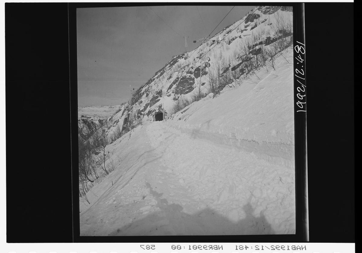 Snørydding langs toglinje, nedsnødde togspor. Tunnel gjennom fjellside.