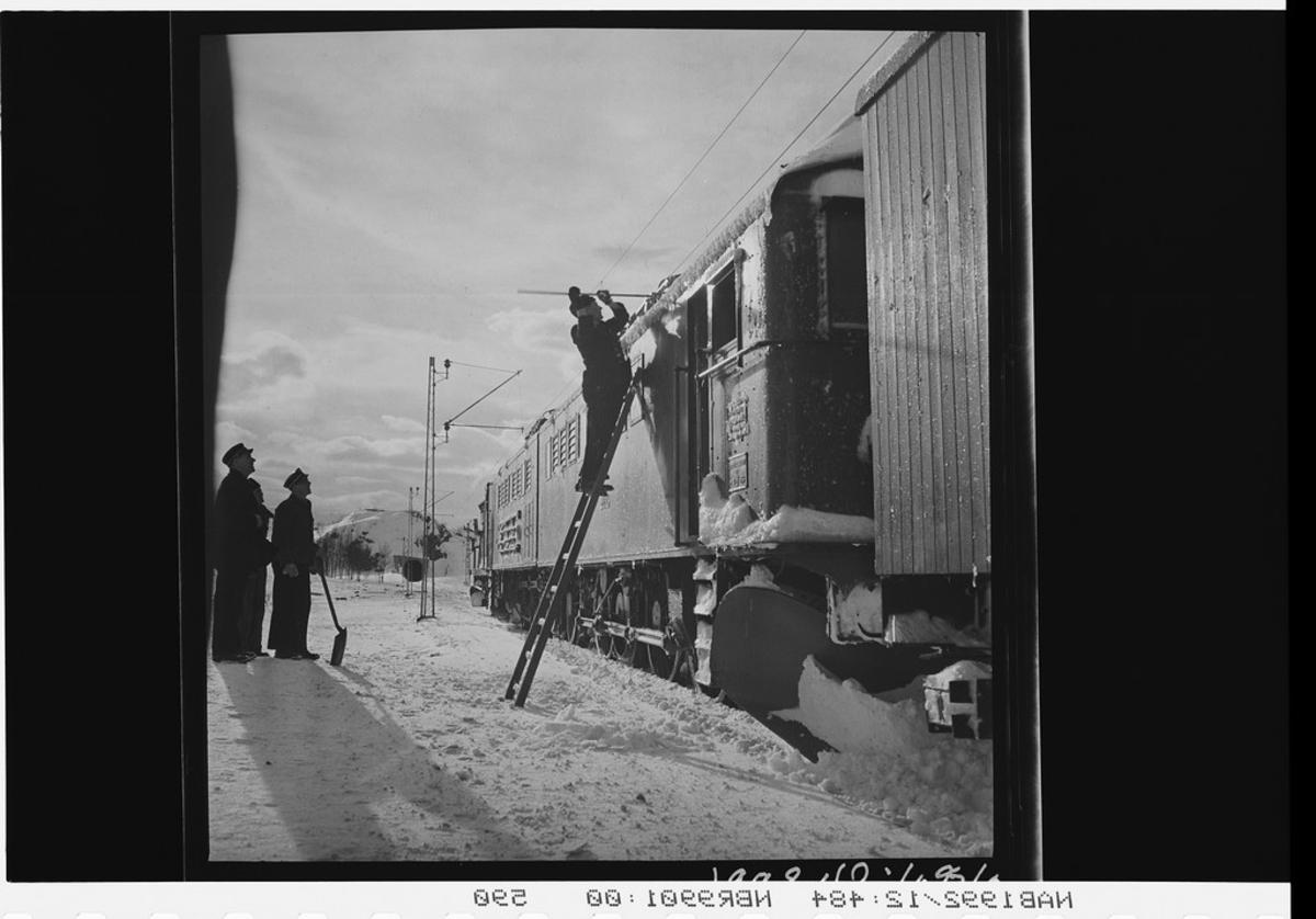 Jernbanepersonell rydder vekk snø fra lokomotiv. Nedsnødde togspor. Loket er et elektrisk lokomotiv av type El.3.
