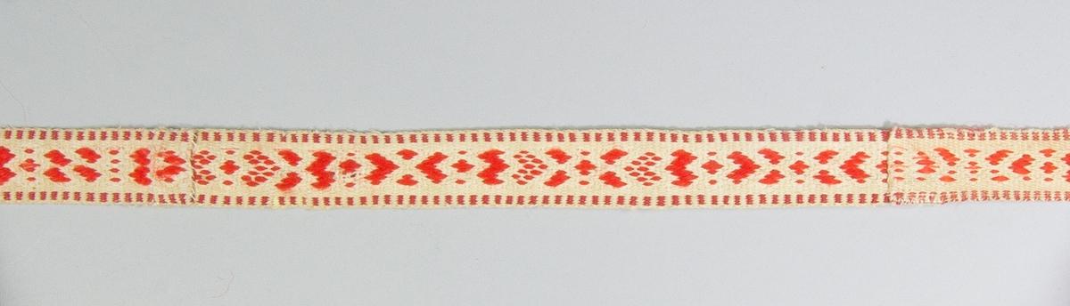 Kjolsäck till dräkt för kvinna från Rättviks socken, Dalarna. Modell med avskuret framstycke. Tillverkad av vitt fårskinn med applikationer av kläde i rött och grönt, fastsydda på maskin med gul tråd. Centralt placerad hjärtblomma med omgivande mindre blommor. Broderi utfört med huvudsakligen gult bomullsgarn: sticksöm. Ovanför applikationen fastsytt ett diagonalvävt rött ylleband, dessutom kantat runtom med samma band. Ovanstycke av rött ylletyg, vävt i kypert. Foder av rött bomullstyg, vävt i kypert. Bakstycke av vitt fårskinn. Fyra fastsydda bollar av rött och grönt ullgarn, en i varje hörn. Axelband handvävt, med plockat mönster i rött ullgarn på vit botten.