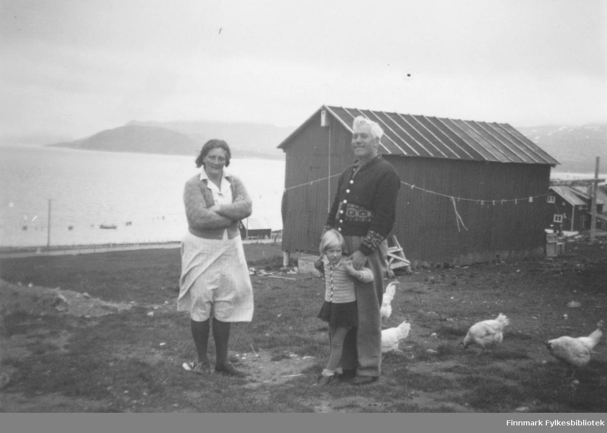Skolestyrer Isak Leiros og hans kone Svanhild. De står sammen med sitt barnebarn eller datter?. Det går høns rundt dem. Bak dem står en låve, og man ser noen hus til høyre i bildet. På sjøen ligger det noen båter