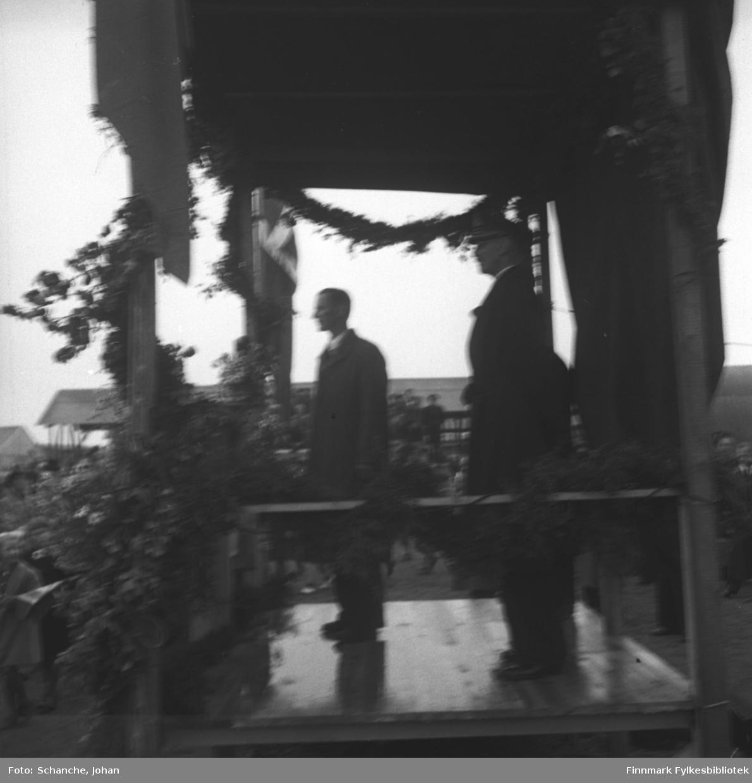 Kongebesøk i Vadsø:  Ordfører Bjarne Pedersen hilsen Kongen velkommen til Vadsø. Både Pedersen og Kong Haakon VII står på en talerplattform som er dekorert med flagger, blomster og bjørketrær.  Folket har samlet seg rund plattformen.  Bildet er uskarp.