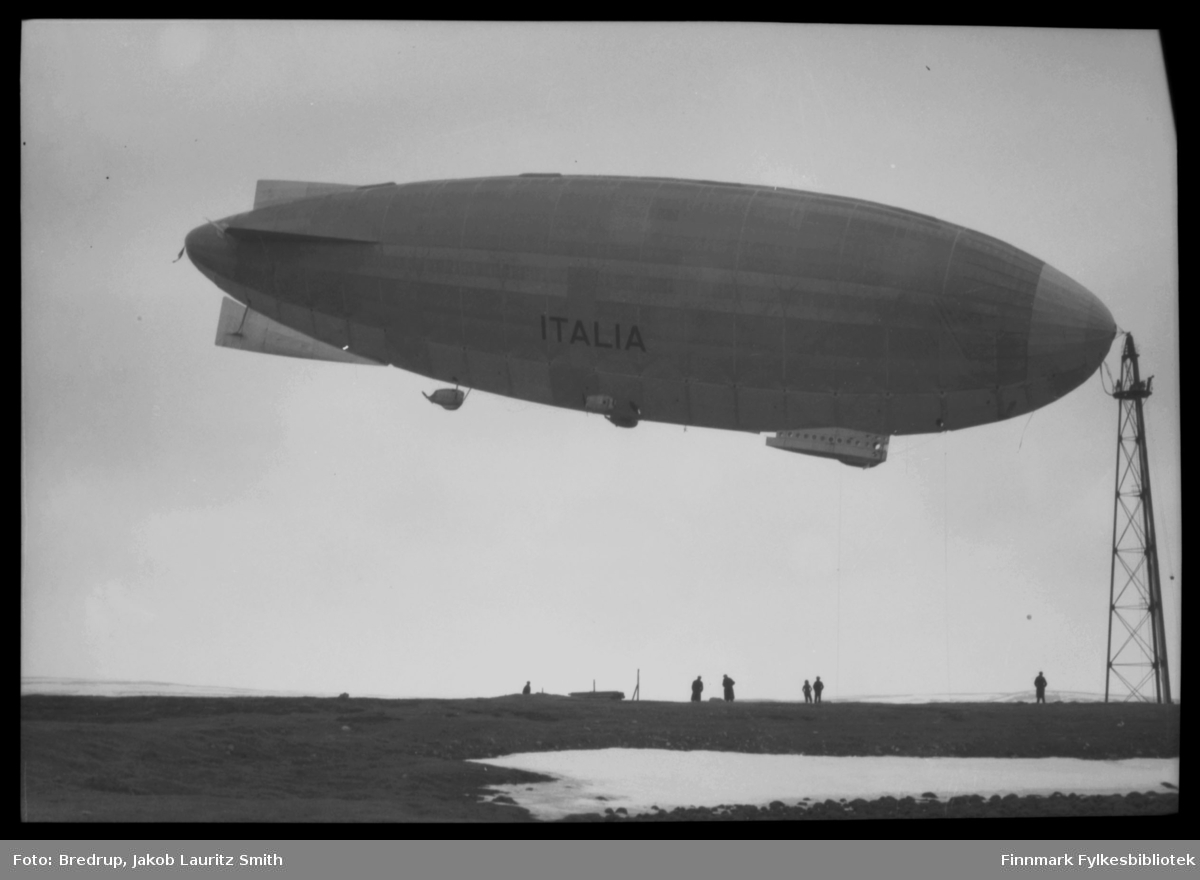 Luftskipet Italia forankret i luftskipsmasta på Vadsøya.  Hele masta er med på bildet, og vi ser også noen mennesker nede på bakken.