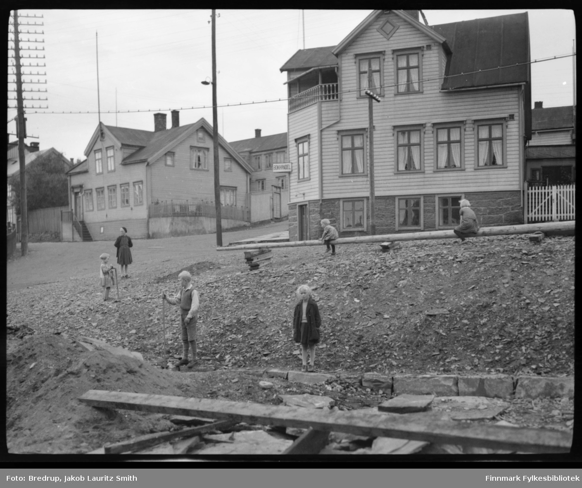 Barn leker i et veikryss mellom Havnegaten, Tollbodgaten og Theatergaden i Vadsø sentrum.  Fotografen har stått omtrent der Rådhuset står i dag.  Til høyre Kildahl Olsen Bog- Papir & Tapethandel, etablert i 1876. Omtrent her står SparebankEN i dag. Til venstre Peder L. Persens bolighus som i 1935 ble løftet opp og ny sokkeletasje bygget på, dit Vadsø ekviperingsforretning flyttet i 1942.  Peder Johansens Kjøtt og Fisk hadde også forretning i sokkeletasjen.  Huset brant ned 23. august 1944.  Ekviperingen står på samme sted i dag.  Helt til venstre skimtes Latmannsgjerdet, andre gjerder og gårdsrom.  Barna på bildet er antakelig sorenskriver Bredrups barn.  Fotografen har stått ved Brodtkorbgården, som ble kjøpt inn til sorenskriverbolig i 1934.  Bredrup-familien flyttet inn dette året.  Det ser ut som det pågår restaureringsarbeider på tomta.