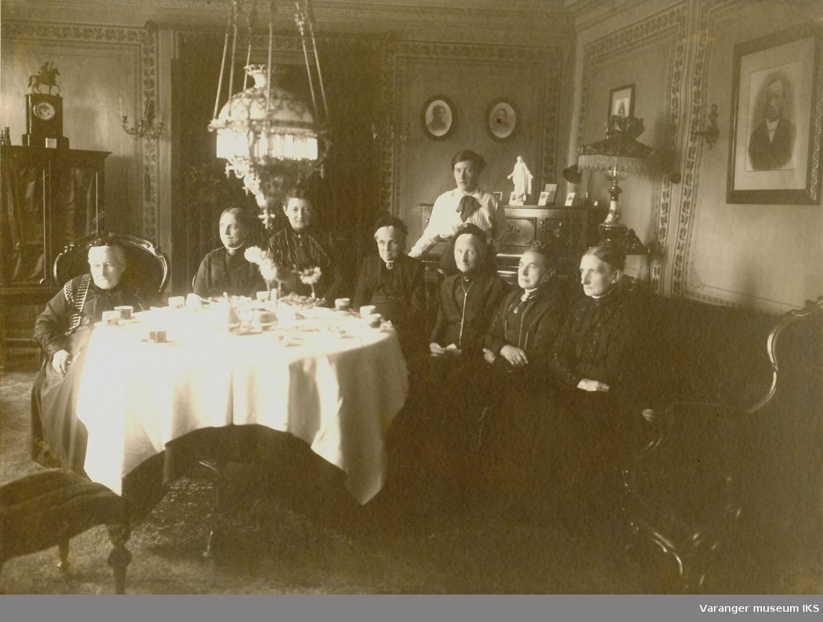 I stuen til Esbensengården i Vadsø sentrum. Ca 1890-1900. Rikka Dahl , Andrea Esbensen, Tora Dahl, ukjent, Ragna Esbensen, Agnete Esbensen, Marlene, Anna Rein