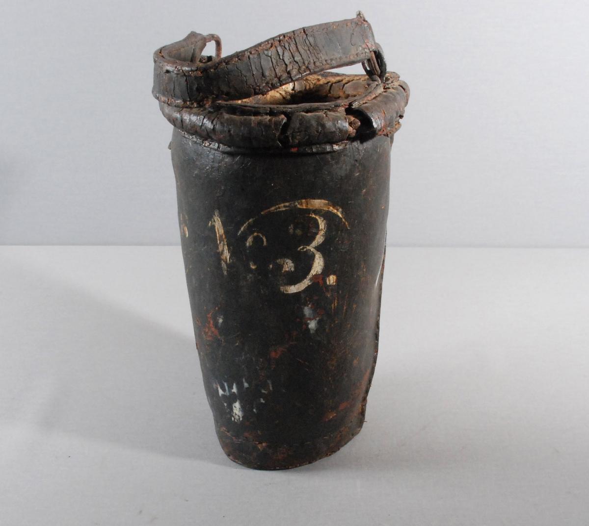 Brannbøtte i lær. Hemper til hank av lær. Lærhank med ringer i metall tredd inn på hempene.