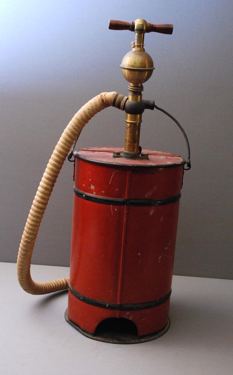 Sylindrisk spann med hank. Pumpe ned i spannet med pumpehåndtaket på toppen, der også slangen med munnstykke er festet. Hengslet lokk på toppen kan åpnes. Malt skjold på beholderen