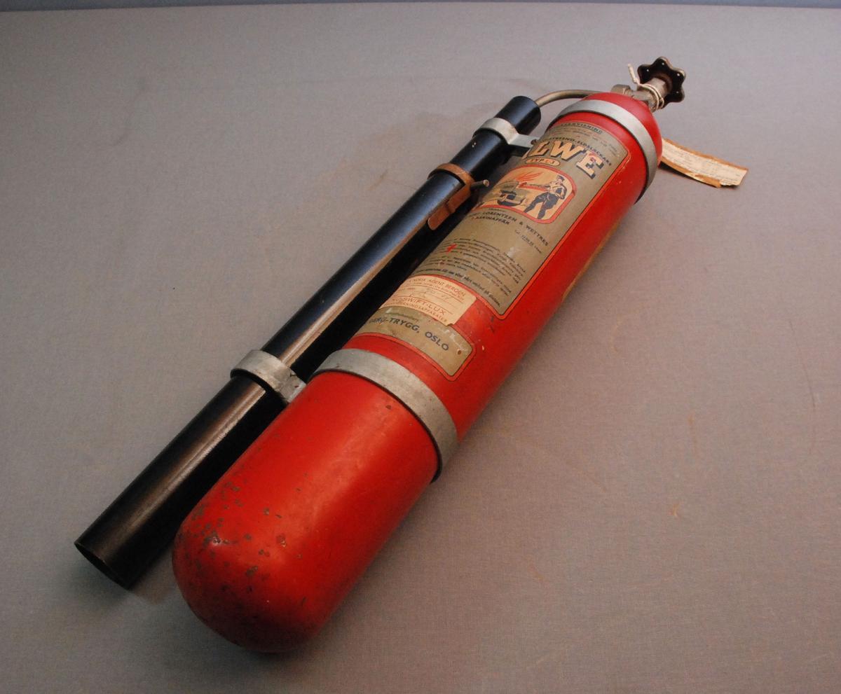 Sylinderformet brannslokkingsapparat med ventilratt på toppen. 2 metallbånd rundt korpus med anordning for feste av teleskopformet slokkerør som er koplet til ventilen på toppen. apparatet er rundt i bunnen.