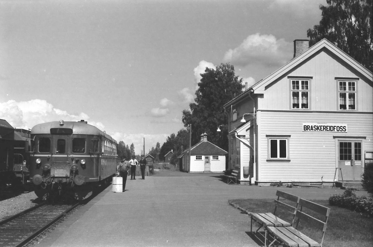 Tog fra Kongsvinger til Elverum og Hamar stopper i Braskereidfoss. Utvendig stasjonsbetjent lemper gods, mens togfører (overkonduktøren) og tjenestegjørende stasjonsmester (txp) samtaler.