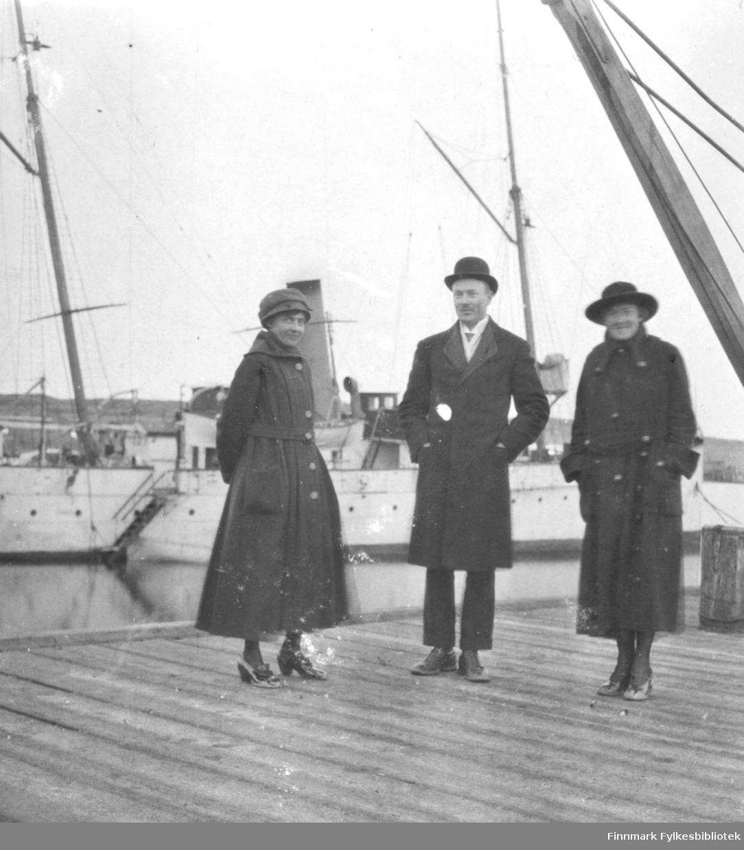 Tre personer på dampkipskaia i Vadsø i bakgrunnen et dampskip