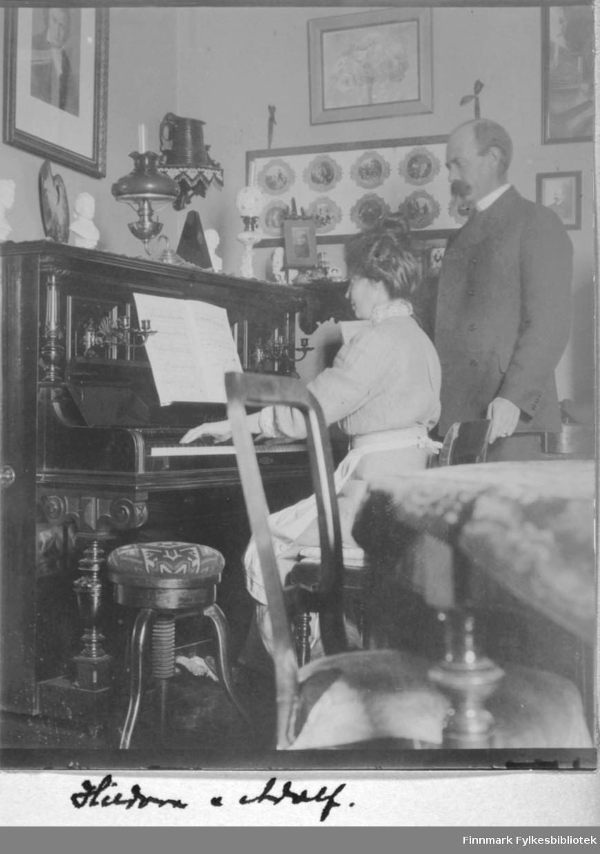 Kvinne som spiller piano, mann som tilhører. 'Hildur [?] og Adolf'