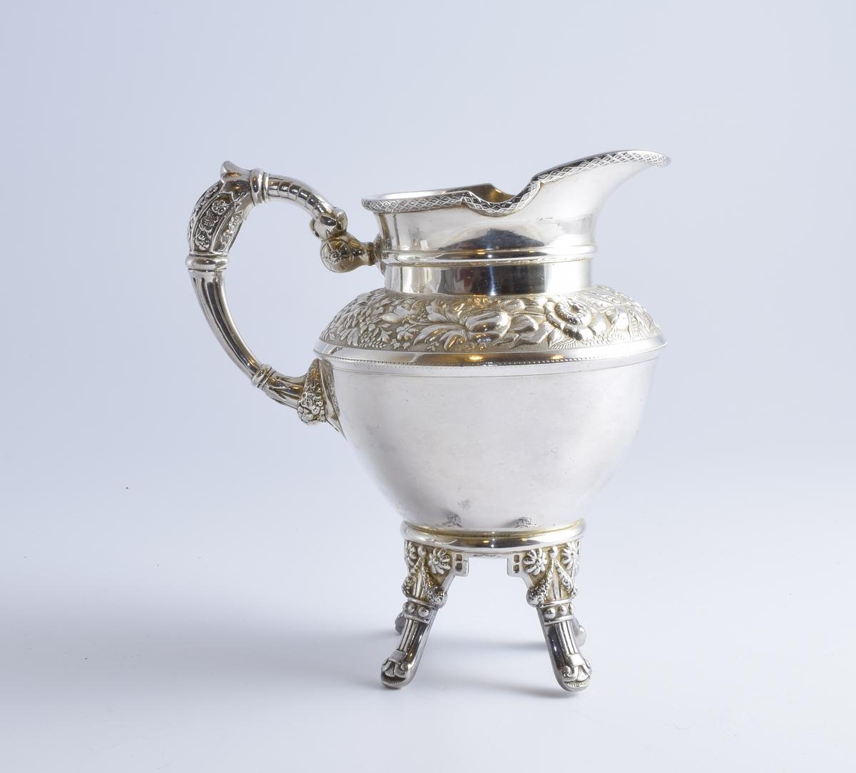 Fløtemugge i sølvplett med blomstermotiv. Muggen er del av et sett med to kanner og en sukkerskål.