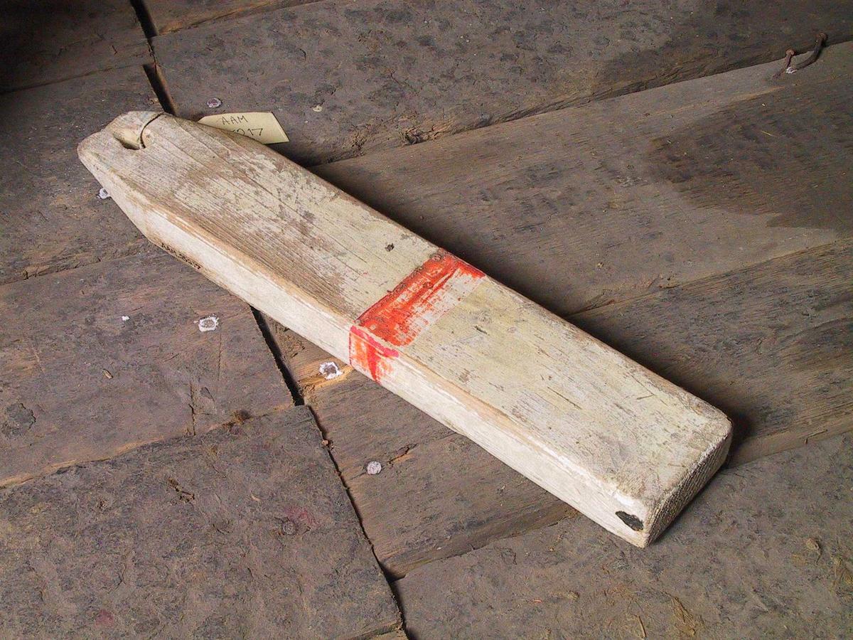 Vøle til hummerteine, laget av ett stykke tre. Hvitmalt med et rødt bånd rundt midt på.   Et stykke 4 x 2 tommes tre, tilspisset, m hull.