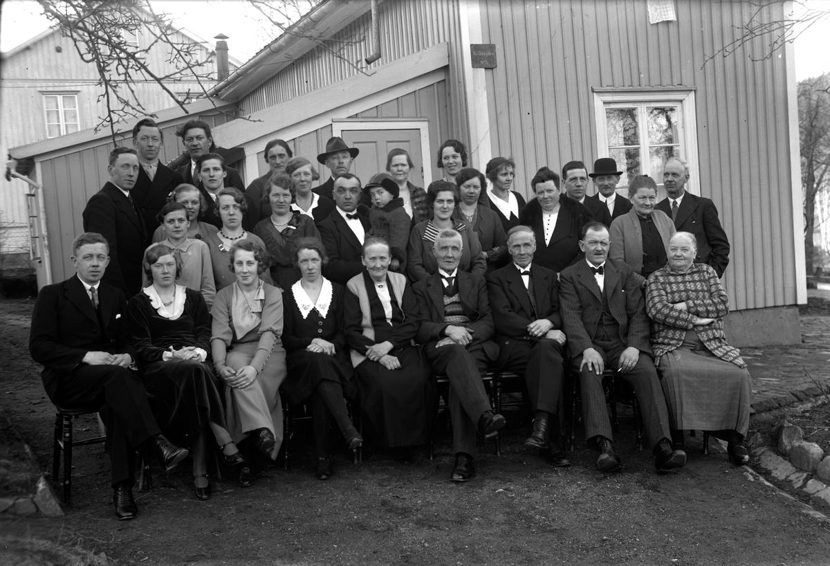 """Släktbild utanför ett hus i Jönköping. På en skylt på husgaveln står """"Kv Odygden nr 3"""". Nedre raden från vänster: Bodin (6), August Öden (7). Andra raden: Hulda Öden (3)."""