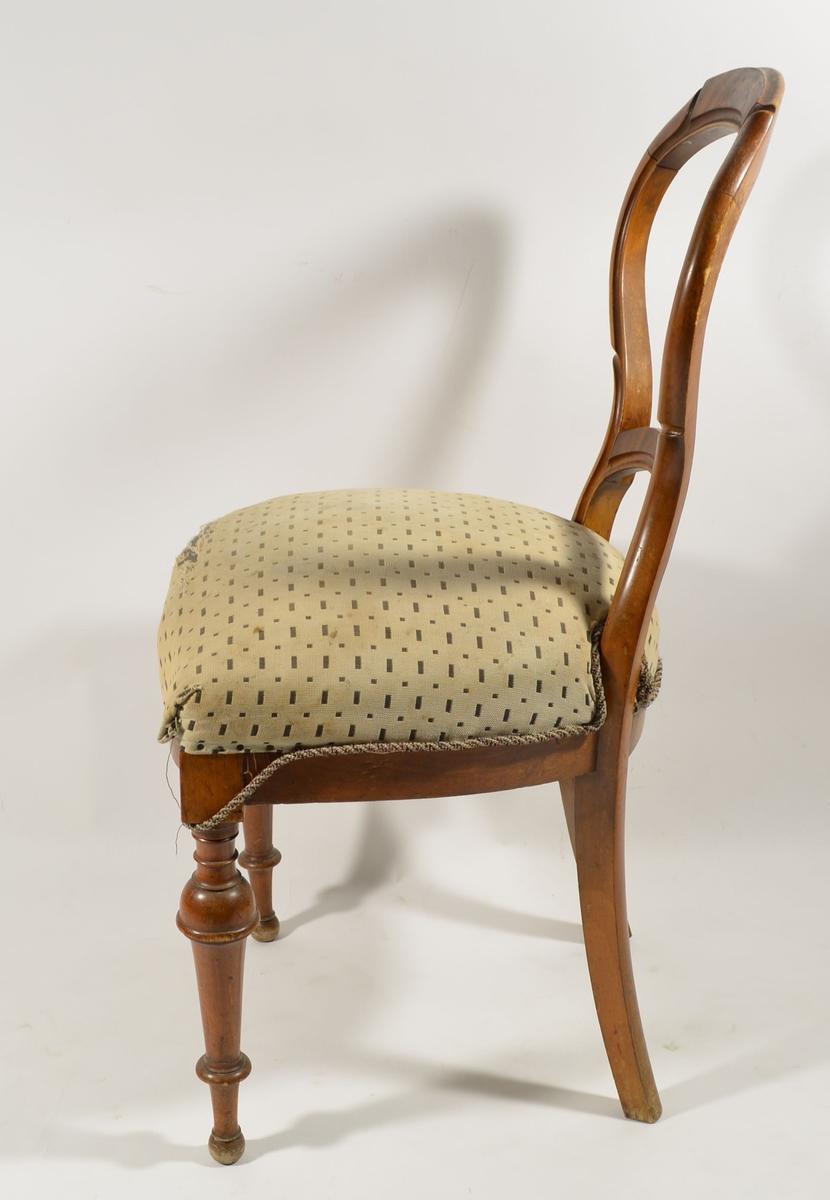 Stolramme i tre med avrundet rygg. Stoppet sete trukket i tekstil. Noe slitasjeskader på setestoffet. Gjordebånd dekker undersiden av setet, som er fjæret.