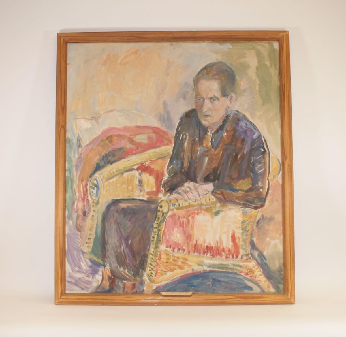 En kvinne sitter i en kurvstol med begge hendene foldet på høyre armlene. Hun har på seg en mørk kjole og ser ut til venstre i bildet. Håret er gredd bakover og festet i en knute i nakken. Lys bakgrunn med en rød avrundet form bak venstre side av stolen.