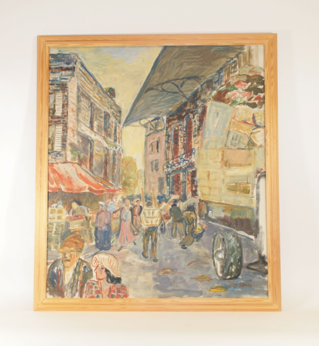 Motivet viser en gatescene, med en gate som går innover fra forgrunnen.  En murbygning i fire etasjer reiser seg til venstre for gaten, en rød baldakin strekker seg ut over gaten over den første etasjen. To murbygninger til høyre. Bygningen fremst til høyre har et tak som strekker seg noe over gaten. I forgrunnen ser man til venstre i bildet to mennesker i forgrunnen, fra skuldrene og opp;  en kvinne og en mann, begge med hatt. Kvinnen snur seg mot mannen. Til høyre ser man bakre del av en lastebil med planet fullt lastet av esker og annet. Mennesker går på gate både innover og utover i bildet. Et fokuspunkt er en mann som bærer en stol eller kurv på ryggen midt i gaten (midt i bildet). Penselstrøkene er markerte, og fargebruken er sterk.