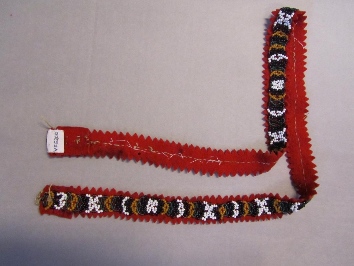 Perlebelte med botn av klede med utstansa sikksakk langs langsider. Band tredd av småperler i ulike farger påsydd med lintråd. Mangler spenne.