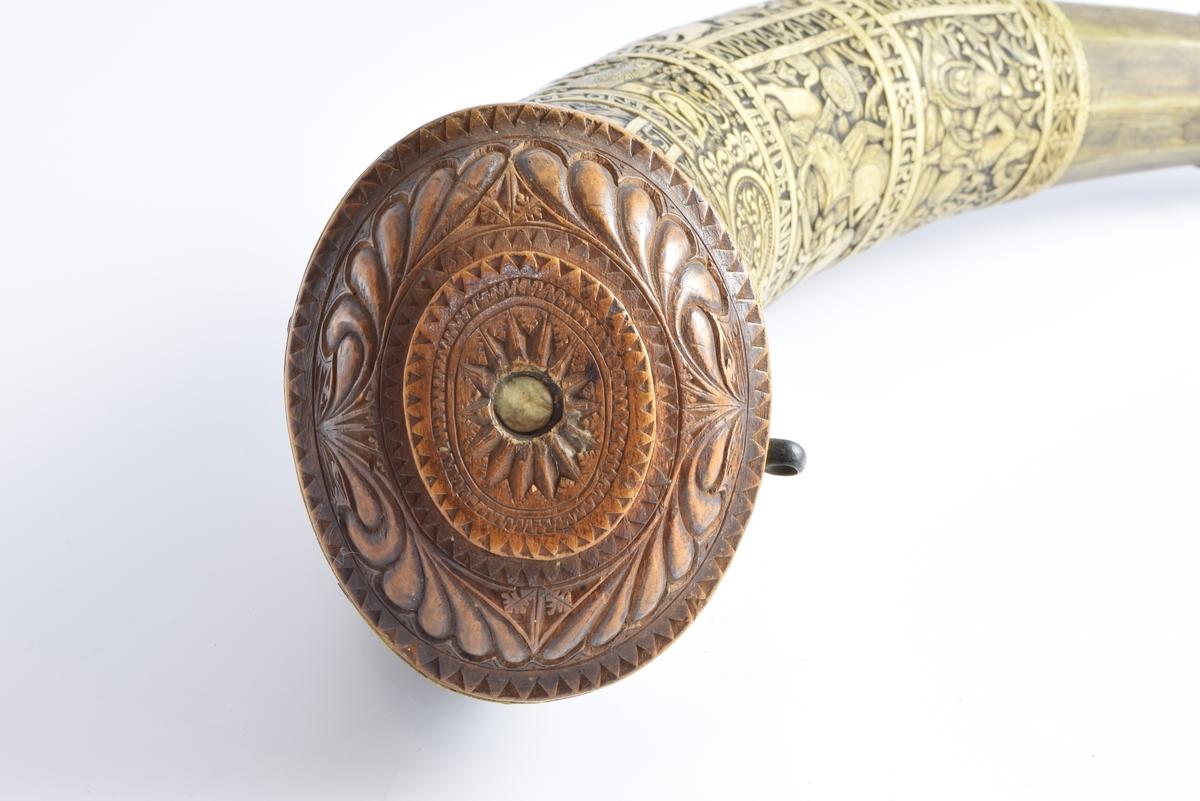 """Rikt dekorert horn med skårne dekorasjoner i fem horisontale belter og flere små figurfelt med religiøse motiv. I det første beltet nærmest munningen er det fire figurfelt som viser: 1. Adam og Eva, 2. Jakob og engelen, 3. Daniel og """"dragen"""", 4. Speiderne. Det andre beltet har tre figurfelt som fremstiller ryttere til kamp. I det tredje beltet er det en sirkel som viser Absalon som henger etter håret. På hver sin side av sirkelen vises Samson og løven og David og Goliat. Det fjerde beltet viser ryttere til kamp og det femte beltet nærmest spissen, viser en fjellbonde og en kjøpmann. Mellom figurfeltene er det en rekke innskripsjoner."""