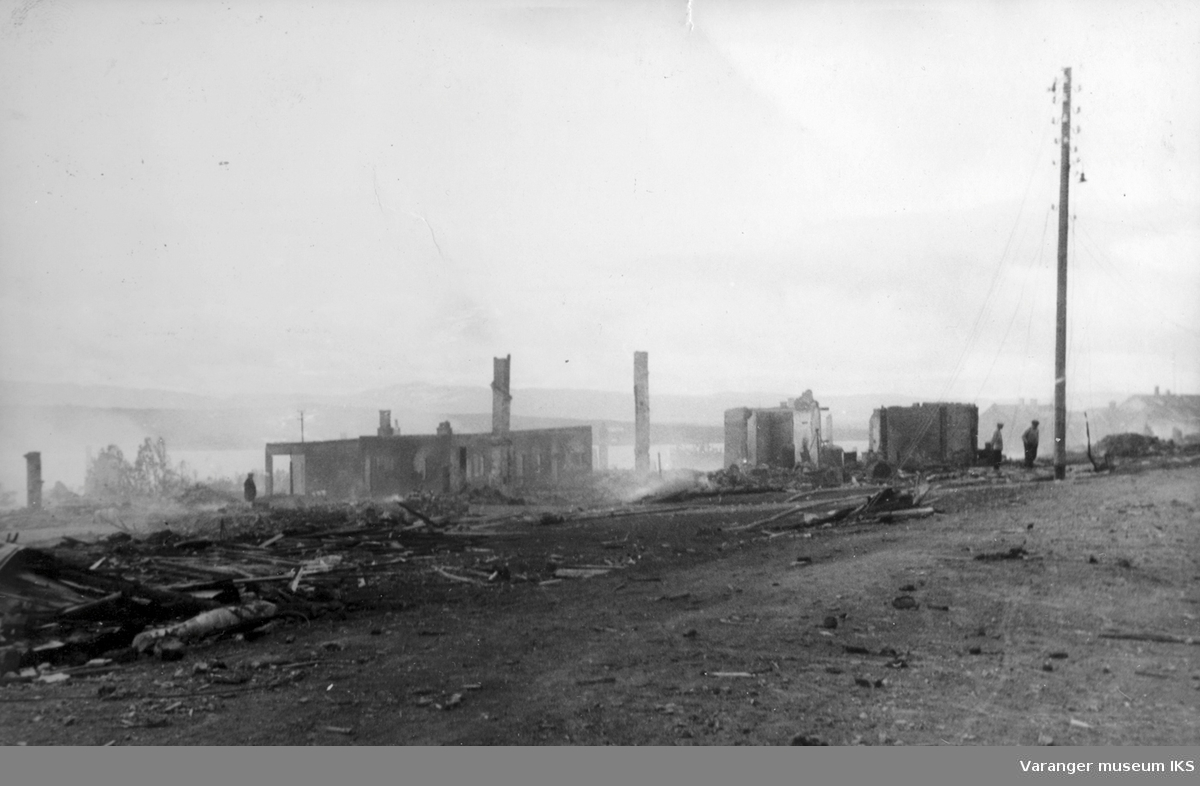 Oscarsgate i Vadsø etter de alliertes storbombing av byen, august 1944. Den ødelagte brannstasjonen nærmest til venstre.