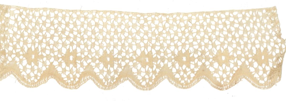 Teknik: Halva spetsen består av en botten av nätbottnar och vridningar. Andra halvan har ett mönster av en rad med rosor arbetade i vävslag samt vinkelformade fält i vävslag som går upp mellan rosorna. Uddarna är kantade endast med tunn vridning.   Denna spets tillhör ryska samlingen.