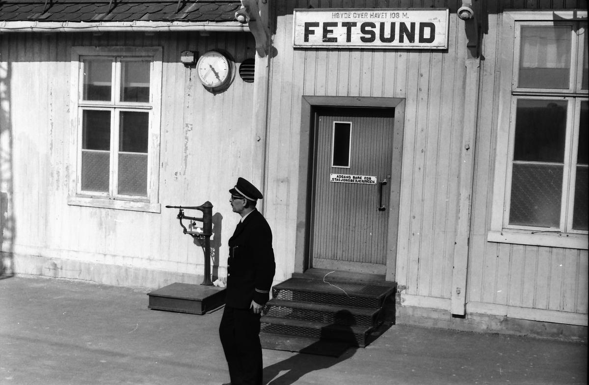 Togfører i et persontog Charlottenberg  - Oslo Ø på Kongsvingerbanen på plattformen på Fetsund stasjon, venter på å gi avgangssignal til lokomotivføreren.