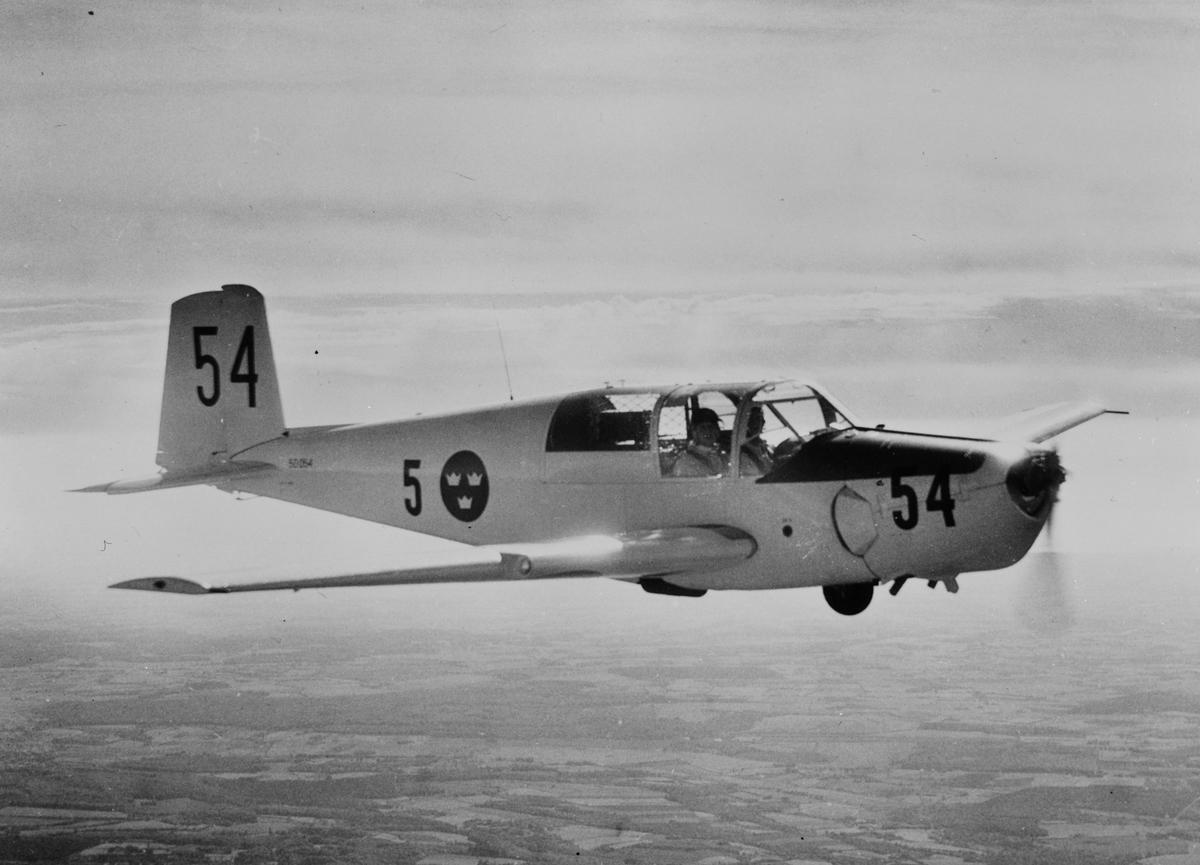 Flygplan SK 50B märkt nummer 54 (50054) från Krigsflygskolan F 5 flyger över landskap.