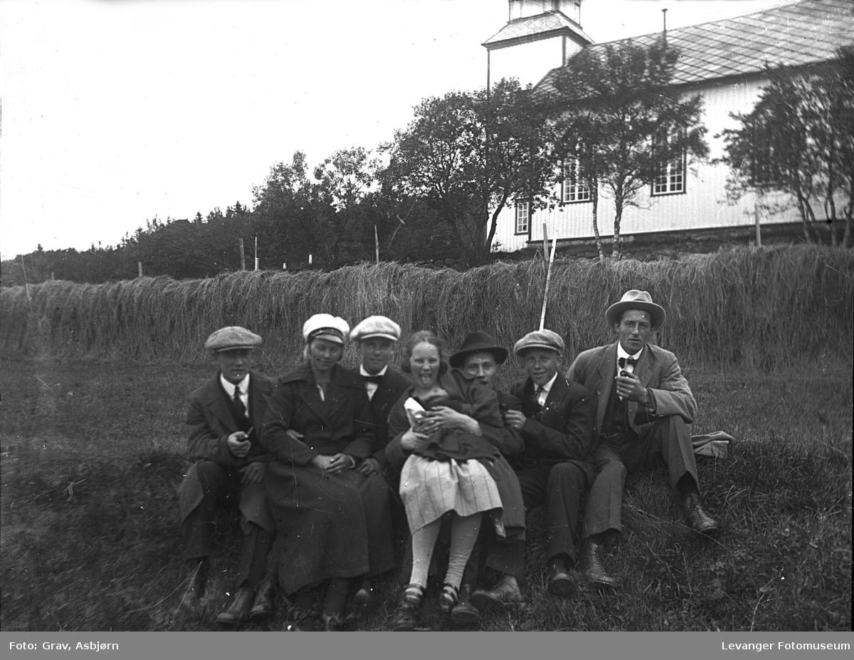 Gruppe på tur, kvinnene med sangerluer, kirke i bakgrunnen.