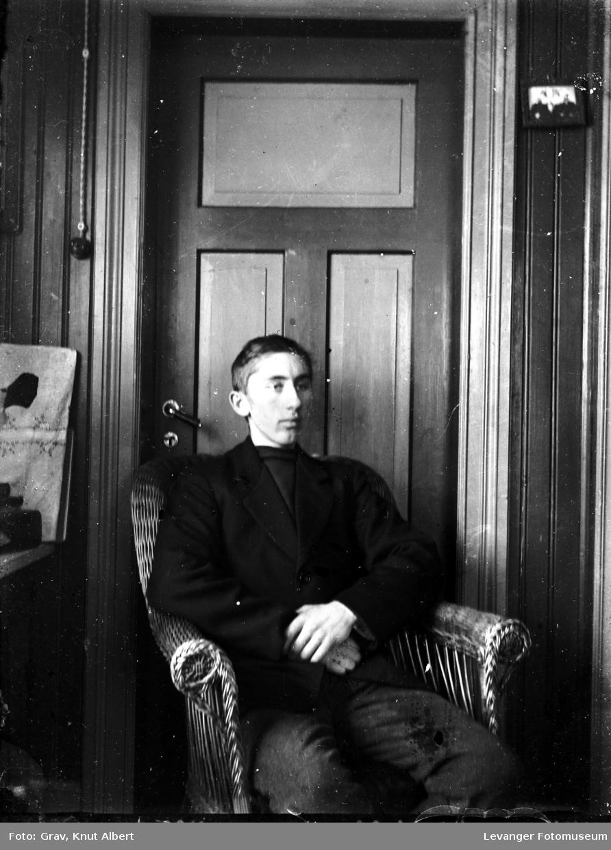 Portrett av en ung mann i en kurvstol foran en dør.