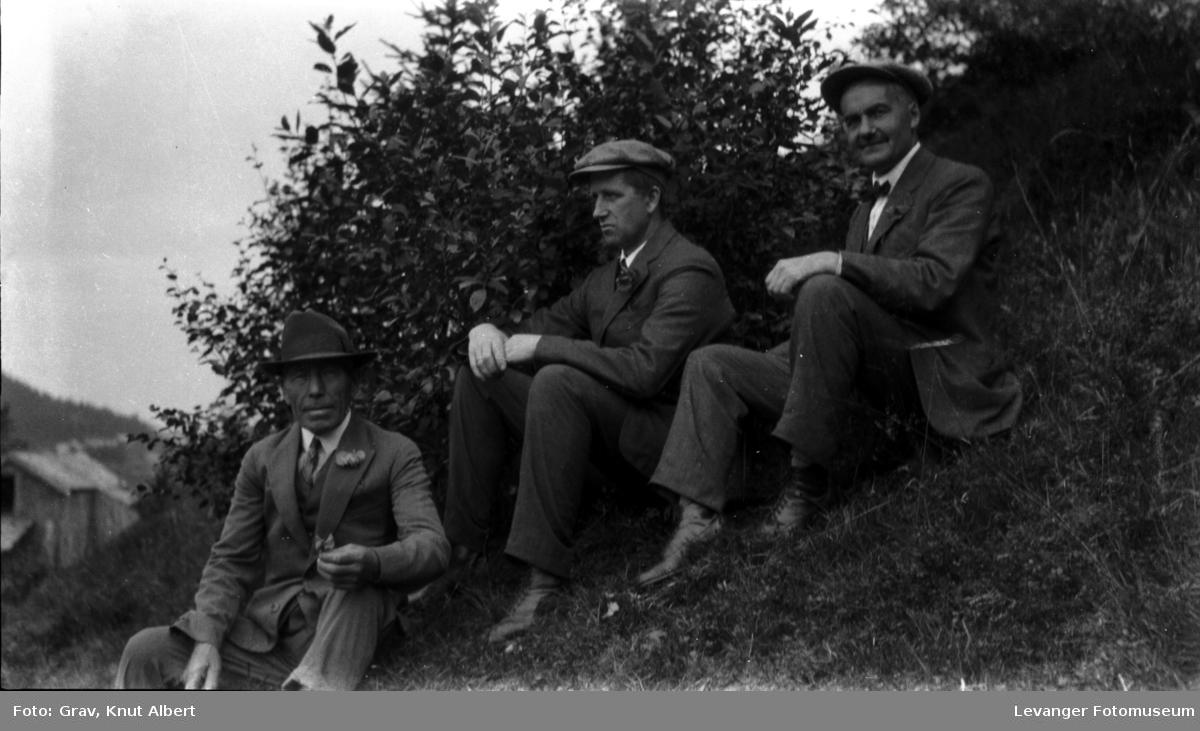Gruppebilde, tre menn sitter i skråning.