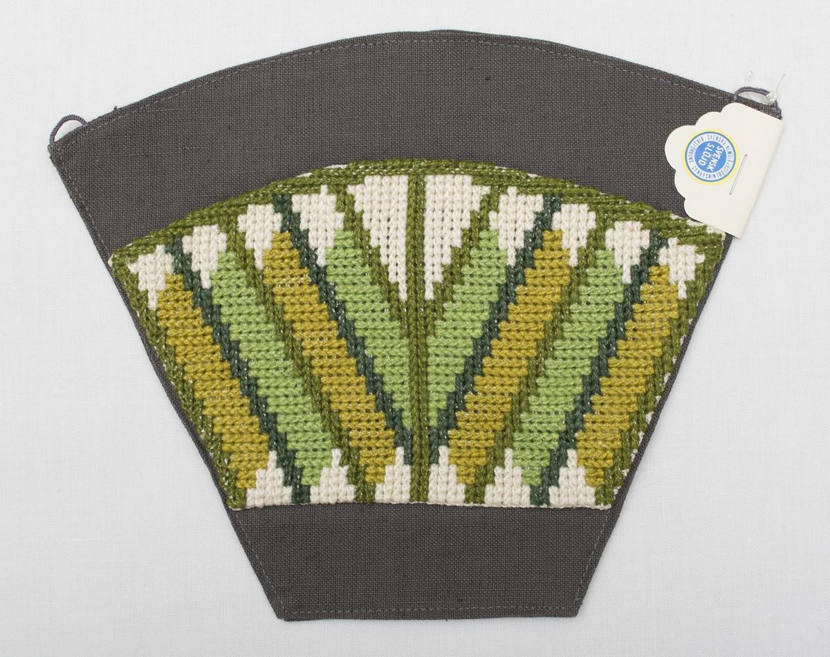Broderad kaffefilterhållare i tvistsöm i olika gröna nyanser, samt vitt. Broderiet är monterat på ett vändsytt grått bakstycke i linneväv, med två halvöglor i langett för upphängning. Föremålet är märkt med SHR-märke. Formgiven av textilkonstnär Kerstin Mauritzson.