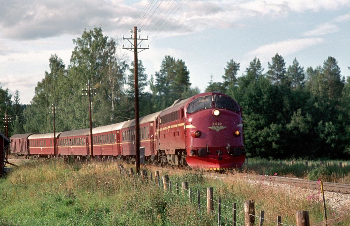 Rørosbanens dagtog Ht 302 Trondheim - Oslo Ø kjører ut fra Koppang stasjon med dieselelektrisk lokomotiv Di 3 622 og vogner type 3.