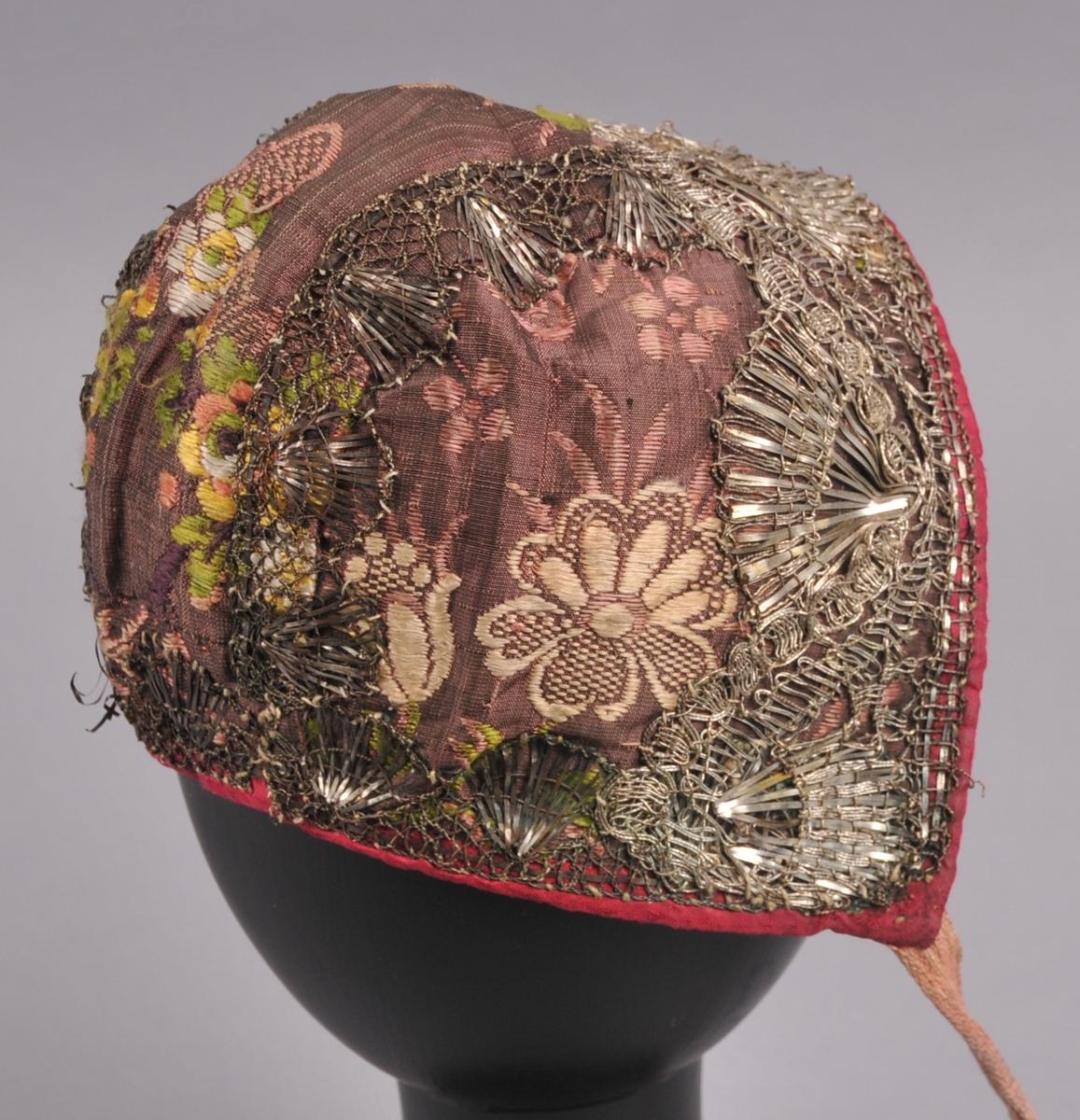 Form: Luve sett saman av tre stykkje. Luva er av silkebrokade, er kanta med raud silke, har ein  breid sylvknipling framme og ein smalar sylvknipling rundt nakken og over saumane bak. Foret er to ulike stofftyper, ei einsfarga og ei med trykt mønster.
