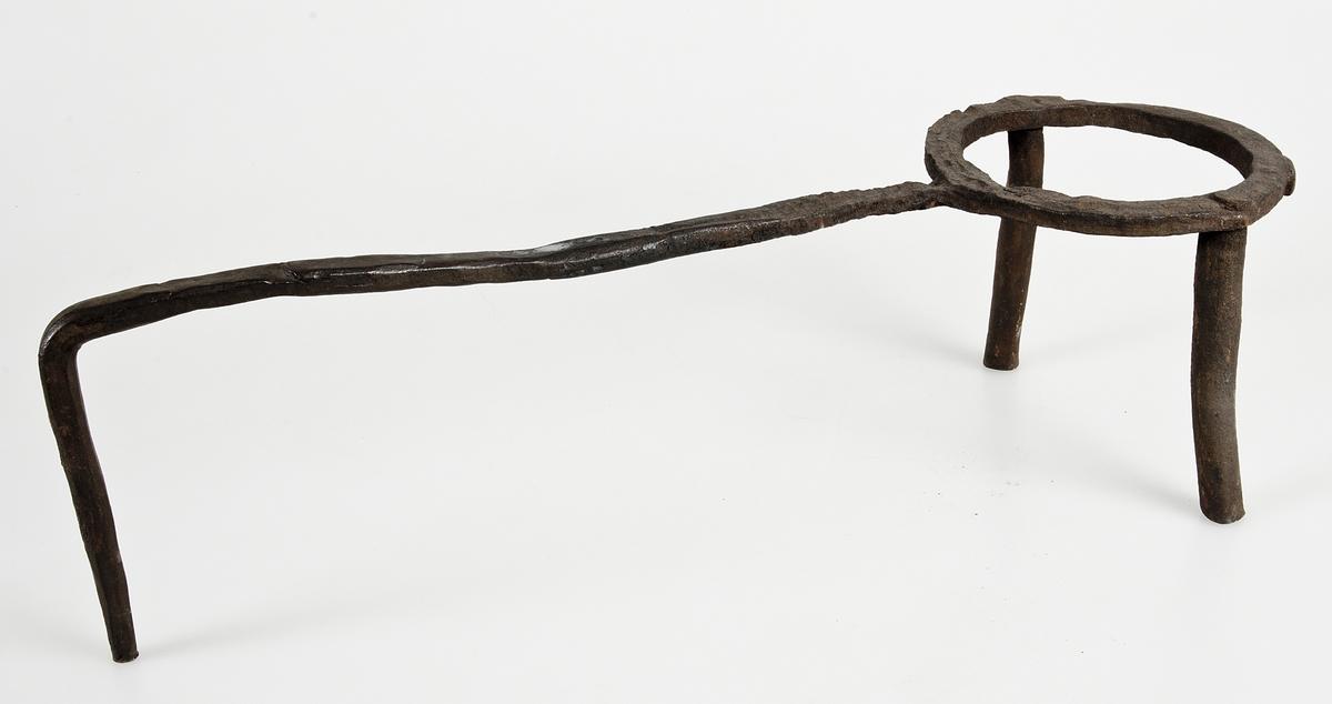 Trefot av järn. Bestående av ring med två fötter, från ringen utgår ett långt handtag, som slutar i en tredje fot.
