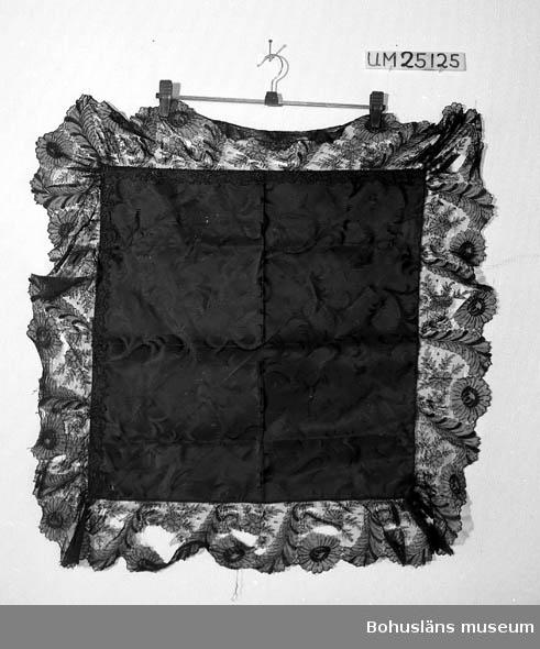 """503 Kön KVINNA Kvadratisk svart sidenschalett med ripsbotten och invävt växtmönster över hela ytan. En 13 cm bred spets är fastsydd med maskin runtom. Längs två av sidorna är dessutom en blommönstrad sydd spets fastsydd för hand intill tygets kant. Spetsarna är maskintillverkande. Tillverkningstid osäker, satt till 1900 ca för att markera att schalen kan vara från slutet av 1800-talet, men troligare från början av 1900-talet. Tyget lagat på tre ställen. Ett litet hål i tyget, flera stora hål i yttersta spetsen. Litteratur; Håkansson, Elin, Sidenhalsdukens bruk och tillverkning ur """"Sörmlandsbygden"""" 1933. Lewis, Katarina, Schartauansk Kvinnofromhet i tjugonde seklet, Uddevalla 1997, sid. 126. Lindvall-Nordin, Christina, Mossrosor och hjärtblomster ur Kulturens årsbok 1969, Lund. museet vävda hos K A Almgrens sidenväveri i Stockholm, uppsats för fortsättningskurs i etnologi, Stockholm 1979."""