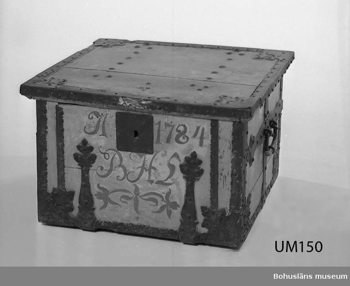 """Ur handskrivna katalogen 1957-1958: Kista. """"A 1784, BHL"""" L.60, Br. 57, H. 38 cm; av trä m. rikt utstyrda järnbeslag. Träet gråvitt, beslagen svarta. Låset saknas. Maskhål. I mycket dåligt skick; träet murket delvis, järnet rostigt, stora delar av beslagen förstörda.  Lappkatalog: 84"""