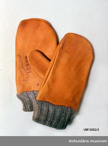 """Gulbrun tumvante av läder med grå resårstickad mudd av ullgarn. På insidan fodrad med trikå, med bottenmaskor i bomull och luddigt skikt av ruggat ullgarn. På högervantens insida stämplat """"LOHUD"""", en bild av  ett hoppande lodjur och siffran 11 (storleksmärkning?) samt skrivet  med bläckpenna """"15,7,o"""" och en otydlig siffra eller bokstav. Vantarna är sammanknutna med en bit lingarn."""