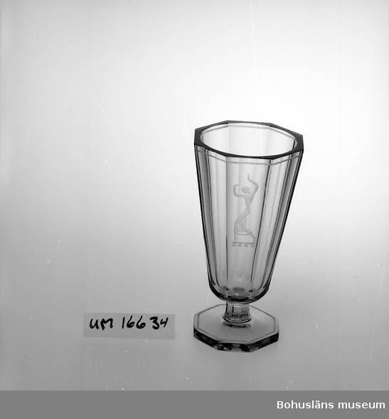 """Vas på fot (fotens diameter 88 mm). Överdelens diameter är 115 mm, höjd 212 mm. Bruntonat glas; åttakantig form. Slipad tunn rand upptill runt kanten. Mattslipad figur i form av dansande kvinna på en av sidans åtta segment. Formgivare Vicke Lindstrand.  Ingraverat i botten """"Orrefors L 1061. A2 . å(?)""""  Vicke Lindstrand (Viktor Emanuel Lindstrand 1904-1983) var anställd på Orrefors glasbruk mellan åren 1928 och 1940. Ca 500 alster i kataloger och andra källor bär Lindstrands signatur. Till detta kommer unika glaspjäser samt ett stort antal hedersgåvor. Vaser dominerar produktionen; motiven varierar, likaså formen. Två företeelser återkommer ständigt - det är vattnet och musiken. Sjöjungfrur, fiskar och dykare blandas med dansöser, musikanter och nottecken. Vickes uppväxt i Göteborg med närheten till havet, hans musikintresse och kantorsengagemang (han startade sin kantorsbana i Tyska kyrkan i Göteborg) kan skådas i hans glas.  Litteratur: Thor, Lars, """"Legend i Glas. En bok om Vicke Lindstrand"""", Liber 1982."""
