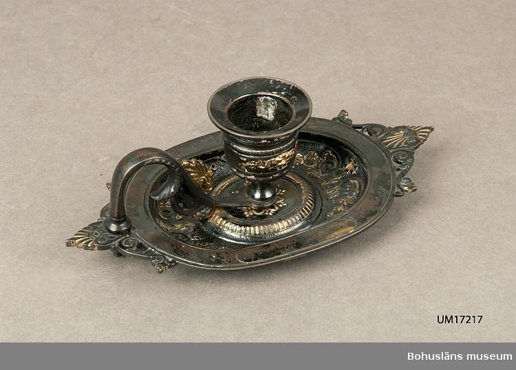 471 Tillverkningstid SENT 410 Mått/Vikt !L 16 X B 8,5 X H 5,5 503 Kön KVINNA 600 Fat med handtag och påskruvad ljuspipa i form av urna,svart med for- 6001 gylld dekor. Troligen från Britta Cullbergs  foräldrar i Göteborg, 6002 Haradshövding Drahenberg. 1:e Antikvarie Kjerstin Cullberg,Bohusläns 6003 museum Uddevalla.